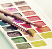Watercolor paints and brush on the table. Vintage retro hipster Stock Images