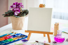 Watercolor paints, brushes , canvas on easel Stock Photography