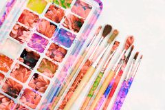 Watercolor paints and brushes, double exposure with flowers, creative art background. The palette of multi-colored watercolor paints and brushes for painting on stock photography