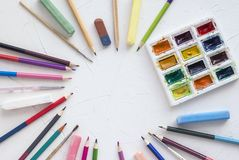 Watercolor paints with brushes for drawing and pencils, chalk on a white table. arranged in a circle stock images