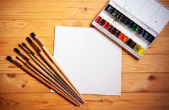 Watercolor paints, brushes for painting and paper sheet on  wooden background Royalty Free Stock Image