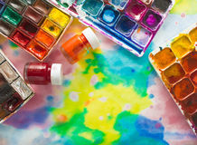 Watercolor paints, brushes and palette on the colorful background. Stock Photos