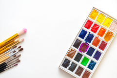 Watercolor paints of different colors with a wide range of brushes. Watercolor paints in a palette of different colors with a wide range of brushes of different Royalty Free Stock Images