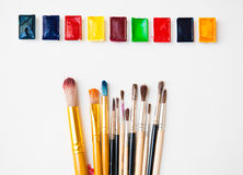 Watercolor paints of different colors with a wide range of brushes. Watercolor paints in a palette of different colors with a wide range of brushes of different Royalty Free Stock Photo