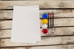 Watercolor paints, paint brushes and white paper Stock Photos