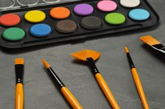 Watercolor paints with paintbrush set. On stone background royalty free stock photos