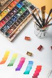 Watercolor paints, paintbrushes and colorful paint strokes in drawing album at designer workplace Stock Image