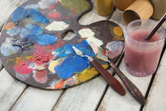 Watercolor paints and palette knives on wooden surface Royalty Free Stock Image