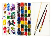 Watercolor paints with pallet and few paintbrushes. Set of used watercolor paints in plastic box with pallet and few paintbrushes in cover isolated on white stock photos