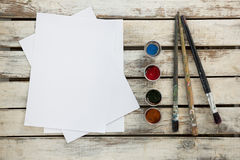 Watercolor paints, paper and paint brushes on wooden surface Stock Images