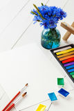 Watercolor paints, pastel crayons and bouquet of cornflowers Royalty Free Stock Photography