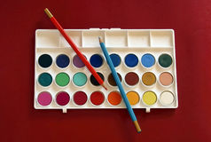 Watercolor paints and pencils. A box of watercolor paints and two colored pencils on a vibrant red background Stock Photography