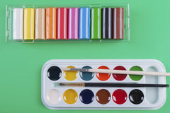 Watercolor paints and plasticine on a green background. Royalty Free Stock Photo