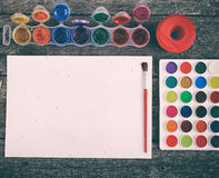 Watercolor paints set with brushes and paper sheet Royalty Free Stock Photos