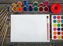 Watercolor paints set with brushes and paper sheet Stock Photos