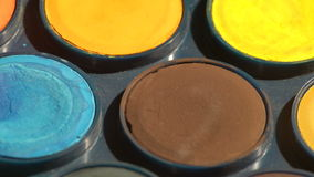 Watercolor paints spinning fast. A close view of a set of used watercolor paints palette turning as a background stock footage