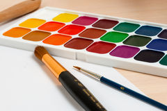 Watercolor paints on the table next to the brushs Royalty Free Stock Photos