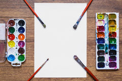 Watercolor paints on wooden background red brush for drawing and white paper Stock Photos
