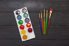 Watercolor palette with brushes on wood background Royalty Free Stock Photo