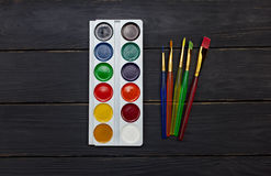 Watercolor palette with brushes on wood background Royalty Free Stock Images