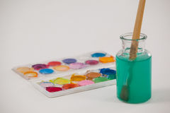 Watercolor palette and paintbrush with blue paint dipped into a jar filled with water Stock Photography