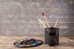 Watercolor palette and pot with brushes Royalty Free Stock Photography