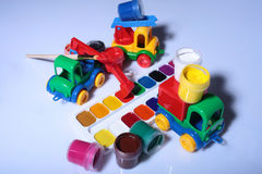 Watercolor palette with toy car. Set of watercolor and gouache paints with brush in palette on grey background closeup with plastic toy cars royalty free stock photo
