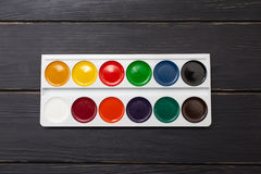 Watercolor palette on wood background Stock Photos