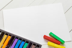 Watercolor pastel crayons and white paper sheet of sketchbook Royalty Free Stock Images