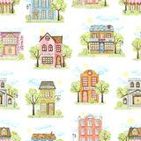 Watercolor seamless pattern with cartoon town houses surrounded by landscape. Seamless pattern with cute cartoon city buildings surrounded by landscape isolated royalty free illustration