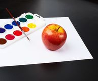 Watercolor set and apple over white paper Stock Images