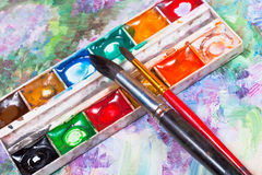 Watercolor set and brushes on oil picture background Stock Photography