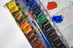 Watercolor Tray. Pans of watercolors and brushes are seen in a plastic tray Stock Image
