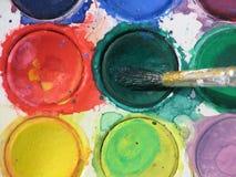 Watercolors. Watercolor paints and brush closeup Stock Images