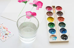 Watercolors, brush and painting of beautiful pink flowers on white background, artistic workplace Stock Image