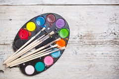 Watercolors and brushes Stock Images