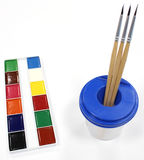 Watercolors, brushes and a glass-pot Royalty Free Stock Image