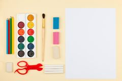 Watercolors, brushes paper on a light yellow background, the concept of holiday, creativity and development of children. royalty free stock photo