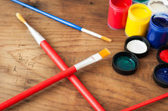 Watercolors and brushes on wooden background Stock Photos