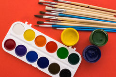 Watercolors gouache and brushes on a red background Royalty Free Stock Photo