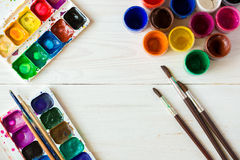Watercolors and paint brush on white wooden background Stock Image