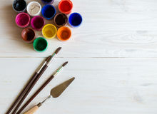 Watercolors and paint brush on white wooden background Stock Photos