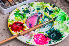 Watercolors and  paint brushes. Water color palettes are green, yellow, red, black Stock Photo
