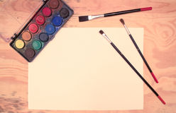 Watercolors, paintbrushes, paper, wooden desk. Flat lay - watercolors, paintbrushes, paper, wooden desk (vintage color shift royalty free stock photo