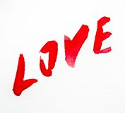 Watercolour painted red word love. The text love in red watercolor in diagonal on a white sheet of paper Stock Photos