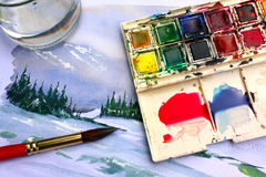 Watercolour Painting. A landscape watercolour painting with the brush, paints and water jar used to paint it Royalty Free Stock Photos