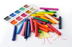 Watercolours and heap of colourfull crayons Royalty Free Stock Photos