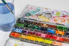 Watercolours mit Pinsel- und Wasserglas Lizenzfreie Stockbilder