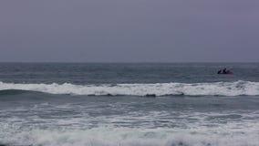 Watercraft con dos personas en olas oceánicas almacen de video