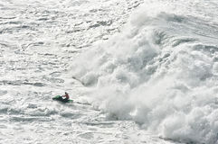 Watercraft escaping from a huge wave Royalty Free Stock Image